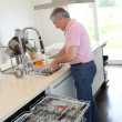 Senior man doing the dishes - Stok fotoğraf