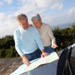 Senior couple looking at road map on car hood — ストック写真