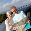 Senior couple looking at road map on car hood — Stock Photo