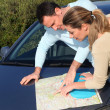 Couple looking at road map on car hood — Stock Photo #6700746