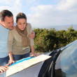 Stock Photo: Couple looking at road map on car hood