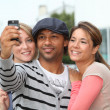 Group of friends taking picture with mobile phone - Stock Photo