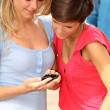 Young women with mobile phone at college campus - Stock fotografie