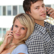 Young couple of students with mobile phone - Stock Photo