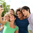 Stock Photo: Group of friends taking picture with mobile phone