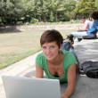 Student with laptop computer in college park — Stock Photo