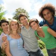 Group of happy students in a park — Stock Photo