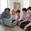 Group of friends sitting with laptop computer — Stock Photo