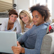 Group of friends sitting with laptop computer - Foto Stock