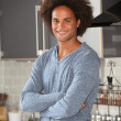 Young man standing in kitchen - Stok fotoğraf
