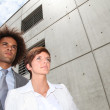 Businesspeople in front of concrete wall — Stock Photo #6702486