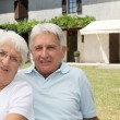 Senior couple sitting in front of a house — Stock Photo #6702692