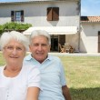 Senior couple sitting in front of a house — Stock Photo