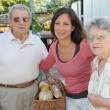 Young woman with couple of elderly persons — Stock Photo