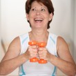 Senior woman lifting weights — Stock Photo