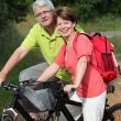 Stock Photo: Senior couple riding bicycle in countryside