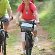 Senior couple riding bicycle in countryside — Stock Photo #6703056