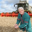 Farmer in wheat field with harvester — Stock Photo