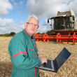 Farmer standing in wheat field with computer — Stock Photo #6703142