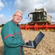Farmer standing in wheat field with computer — Stock Photo