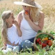 Mother and little girl eating fruits — Stock Photo #6703378