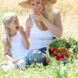 Mother and little girl eating fruits - Stock Photo