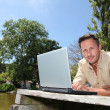 Man with laptop on a pontoon — Stock Photo