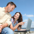 Couple with laptop on a pontoon — Stock Photo