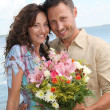 Loving couple with bunch of flowers — Stock Photo