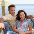 Loving couple sitting on a pontoon by a lake — Stock Photo #6704087
