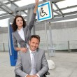 Businesswoman with man in wheelchair - Stock Photo