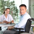 Man in wheelchair with doctor — Stock Photo #6704885