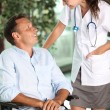 Man in wheelchair with doctor — Stock Photo #6704893