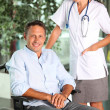 Man in wheelchair with doctor — Stock Photo #6704898