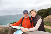 Senior couple looking at map on a rambling day — Stock Photo