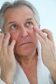 Senior man doing a face massage — Stock Photo