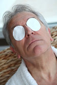 Senior trying to ease eyes pain — Stock Photo