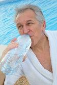 Senior man dinking water from bottle — Stock Photo