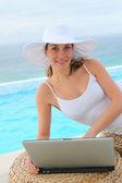 Beautiful woman using laptop computer by swimming-pool — Stock Photo