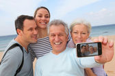 Family taking picture at the beach — Stock Photo