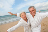 Senior couple in bathrobe at the beach — Stock Photo