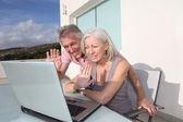 Senior couple waving at webcamera on laptop computer — Stock Photo