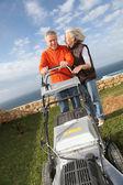 Starší pár, sekání trávníku — Stock fotografie