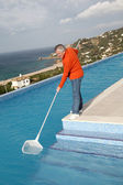 Senior couple cleaning swimming pool — Stock Photo