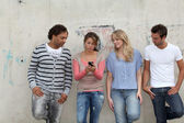 Group of friends standing against wall — Stock Photo