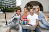 Friends sitting in college campus with laptop computer — Stock Photo