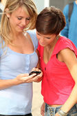 Young women with mobile phone at college campus — Stock Photo