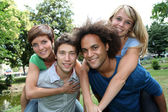 Friends doing piggyback in park — Stock Photo