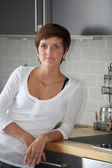 Young woman standing in kitchen — Stock fotografie