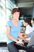 Young woman working on laptop computer — Stock Photo
